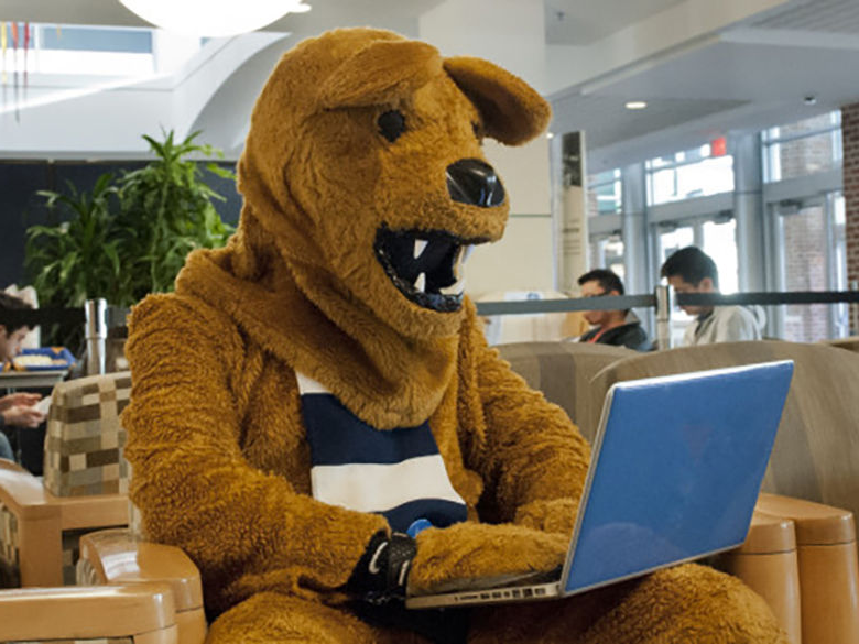 Nittany Lion using a laptop in the 图书馆